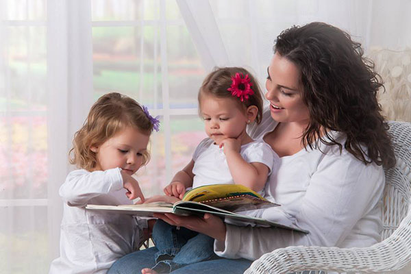 Portrait of Mother reading to two children